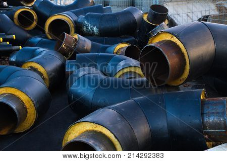 Stored many black steel withdrawal pipe with heat insulation on construction site close up in a plastic tube wrapper lying pipes for supplying gas heat pressure medium. poster