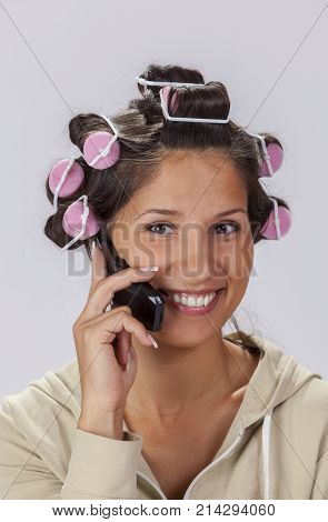 Portrait of a smiling young woman with hair curlers using a mobile phone.