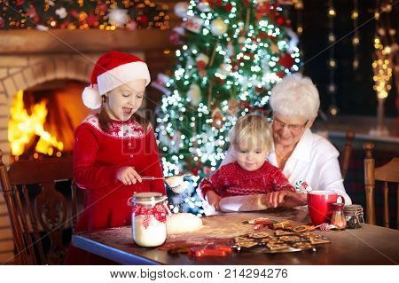 Grandmother and children baking Christmas cookies at fire place and Xmas tree. Kids and grandma bake sweets. Family with kids celebrating Christmas at home. Boy and girl cooking. Generations love.