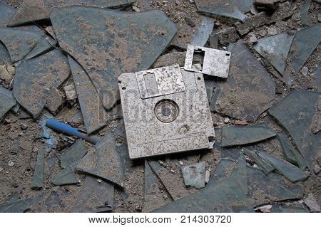 Destroyed and abandoned vintage floppy disc. Forgotten technologies - 3.5 inch disk in plastic case on broken glass.