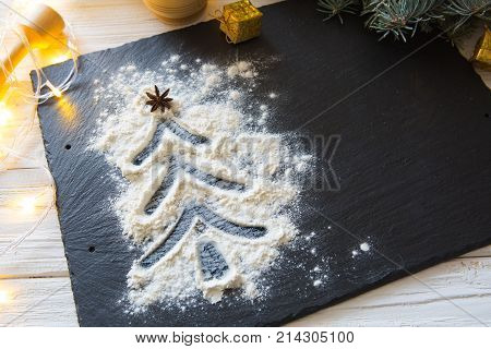 Christmas Tree Decorated With Snow From Flour On The Black On Shale Food Board Background. Merry Chr