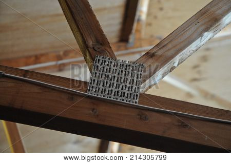 Metallic timber truss on a wooden roof structure