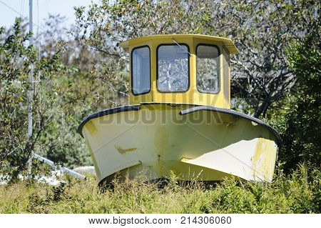 Cuttyhunk Island Massachusetts USA - September 2 2011: Dilapidated boat sitting in patch of weeds