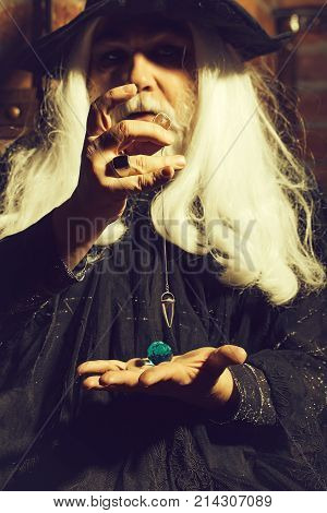 Old man wizard with long gray hair beard in black costume and hat for Halloween holding blue gem stone and silver pendant for hypnosis on wooden background poster