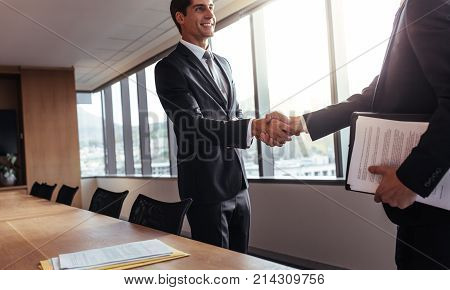 Two business men shaking hands after a successful meeting in the office. Greeting dealing merger and acquisition concept.