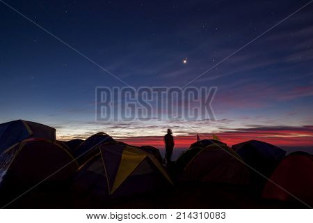 camping man standing in camping area against beautiful colorful sun rising sky