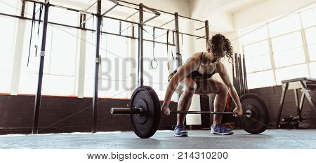 Healthy young woman lifting a barbell at the gym. Fit female athlete exercising with heavy weights at cross training gym.