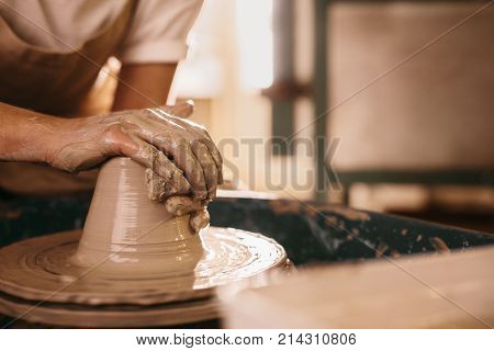 Potter making a clay object on pottery wheel in workshop. Craftsman moulding clay with hands on pottery wheel.