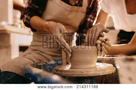 Woman potter teaching the art of pot making. Women working on potters wheel making clay objects.