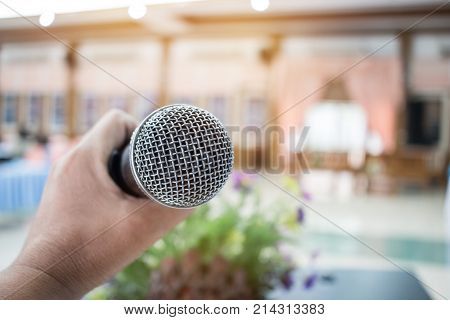 Microphone on abstract blurred of speech in seminar room or speaking conference hall light; computer bokeh background; Microphone on abstract blurred of speech in seminar room or speak;