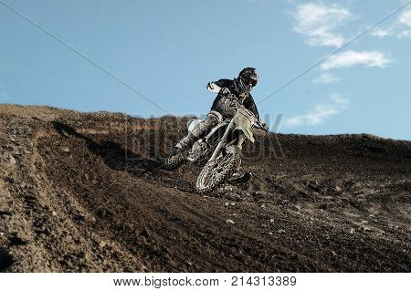 Motocross enduro rider in action accelerating the motorbike after the corner on dirt race track. Extreme off-road race. Hard enduro motorbike. Sky on background