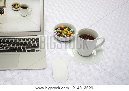 Modern laptop, a cup of tea, lollipops on a white blanket .  the image on the screen comes to life . Duplication shoot. reality and picture on the screen are the same. Concept of escape to real.
