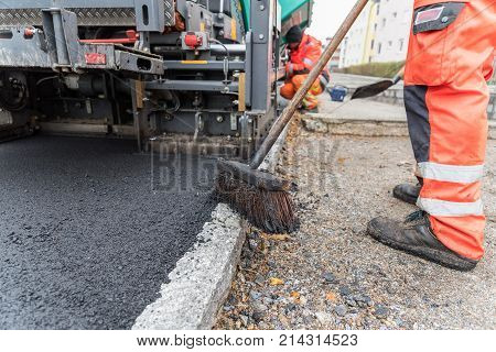 Workers at asphalting works of a sidewalk - close-up