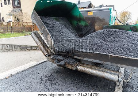 Track paver in asphalting works in action - close-up