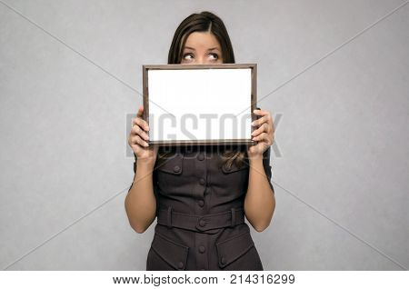 Special offer. Young business woman looks out from blank photo frame holding in her hands. Appreciation document. Grateful letter. Gratitude concept. Accolade. Thank letter.