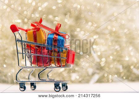 Shopping Christmas and New year gift box and christmas tree in the shopping cart. Holiday Concept