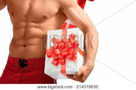 Taking this with me. Studio closeup shot of a ripped and toned young man holding Christmas gifts near his perfect abs. 2018, 2019.