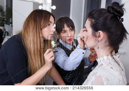 professional makeup teacher training her student girl to become makeup artist. Makeup tutorial lesson at beauty school. Master class. Real people. Visagiste explaining how to apply makeup properly