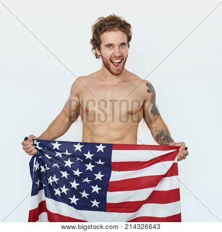 Excited bare-chested man standing on white background and holding USA flag.