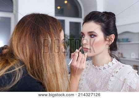 professional makeup artist applying makeup for young woman. Closeup portrait of make up artist at work in her studio. Makeup lips. Backstage photo as visagiste doing lip contour with lip pencil