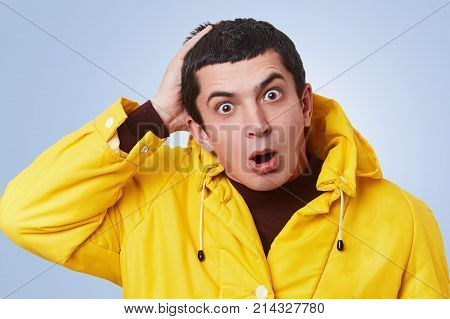 Surprsied Desperated Handsome Man Looks With Bugged Eyes And Widely Opened Mouth, Wears Yellow Anora
