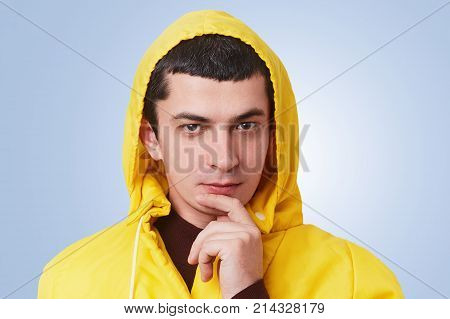 Serious attractive young brunet man looks confidently into camera has thoughtful expression keeps finger on chin wears trendy anorak going to have walk with friends think what take with himself poster
