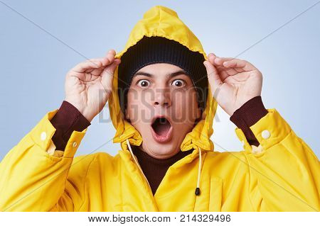 Horizontal Portrait Of Stunned Stupefied Man Wears Yellow Raincoat, Hood And Hat, Looks Out Of Windo