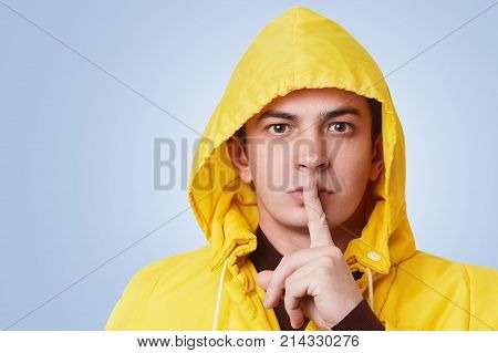 Studio Shot Of Secret Handsome Pleasant Looking Male Keeps Index Finger On Lips, Asks To Keep Secret