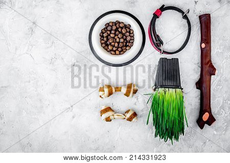 Toys for dog stick and ribbon bone near collar, dry food in bowl and grass in pot on grey background top view.