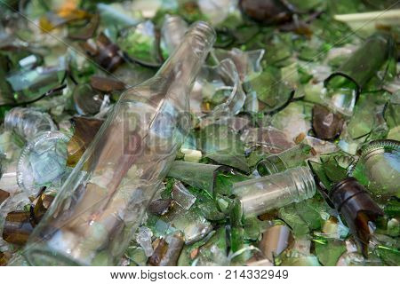 Wine bottle lying on a bed of broken glass having escaped the crusher at a recycling facility. Background