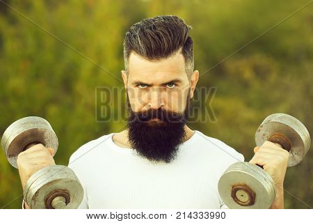 Closeup portrait of one handsome strong young man with long dark haired beard training with dumbells outdoor on green natural background horizontal picture