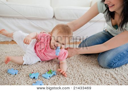 Lovely woman and her baby playing with puzzle pieces while sitting on a carpet in the living room