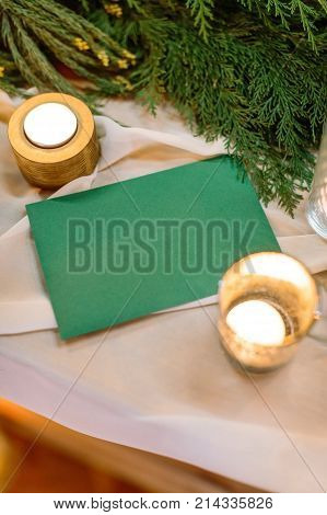 background, wedding polygraphy, winter concept. misterious envelope of deep emerald colour is on the table covered with white silk drapping, burning candles are shining in the golden holders