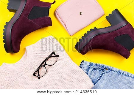 Autumn female clothing - pink sweater, blue jeans, leather handbag, chunky ankle boots, accessories. Top view