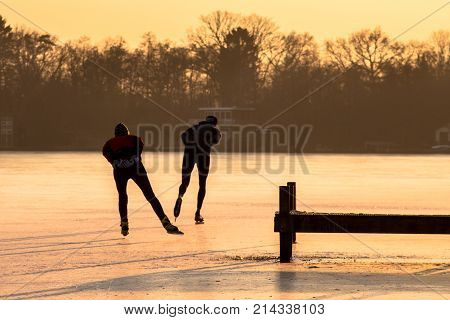 Ice Speed Skating Silhouettes In Orange Light