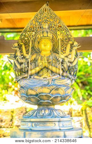 Close up of bronze statue of Kannon in blurred background. Hase-dera, Kamakura, Japan. Hasedera is one of largest Buddhist temples in Kamakura within a pilgrimage circuit of goddess Benzaiten.