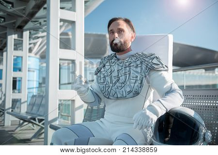 Habit from earth. Relaxed cosmonaut smoking while sitting on bench outside and looking aside with hint of interest in his eyes. Waist up portrait. Copy space on left side