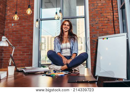 Portrait of smiling female student sitting on table in classroom.