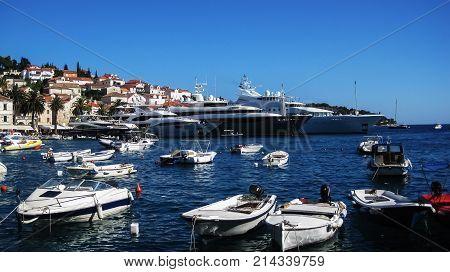 Four mega super yachts on dock in harbor in Hvar at sunny hot day
