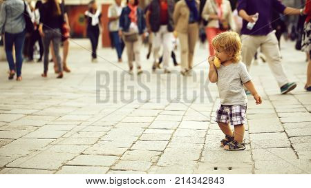 Photo closeup of cute fair-haired blond kid tiny little child baby boy eating bun standing on flag-stone pavement in crowd cityscape on blurred grey background horizontal picture
