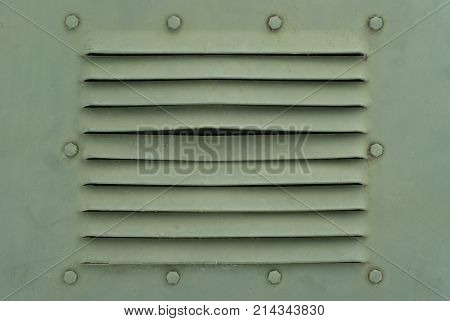 background in the military style: a section of a metal pale khaki wall or shell of some armored vehicle with bolts and ventilation slits