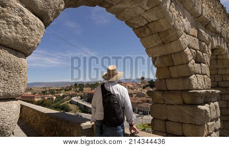 Man standing at Segovia equedoct looking over a villlage in Segovia Spain
