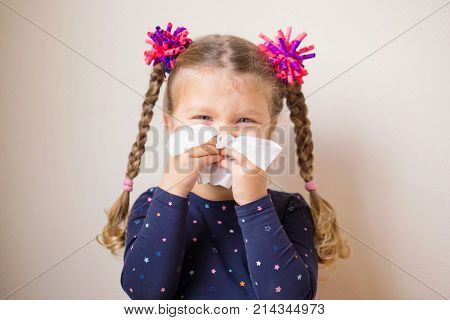 The little girl has a runny nose and blows her nose into a paper handkerchief. Children's cold selective focus on a handkerchief. Acute respiratory viral