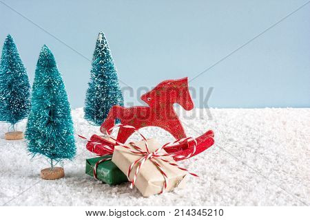 christmas red retro toy horse with pine trees and gift boxes on wooden table covered with snow over blue background. christmas or happy new year holiday decoration