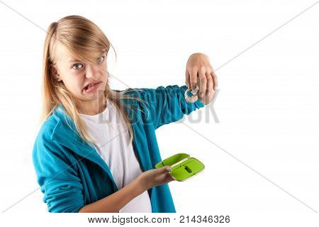 Young girl holding a hearing aid hates it and grimacing. Isolated on white background.
