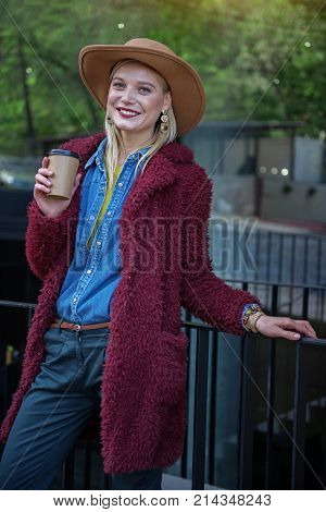 Portrait of cheerful young woman having coffee break on street. She is standing near underground pass and smiling. Girl is wearing autumn coat and hat