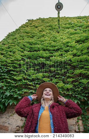 Low angle of excited blond lady observing green clambering plant on roof of the building. She is touching her hat and laughing. Copy space