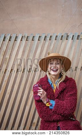 Waist up portrait of joyful young woman relaxing near wood palisade. She is looking forward and laughing. Copy space in left side and above