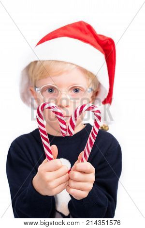 Love Christmas: A cute 4 year old boy wearing glasses is holding two candy sticks, forming a heart shape on a perfect white studio background. Focus on candy sticks and hands.