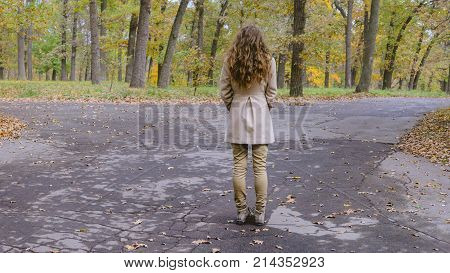 Young woman has decision at the crossroad through autumn colorful forest. She making decision which way to go.